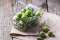 Food basket of brussels sprouts and rosemary on old wooden table see series Stock Image