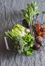 Food basket with fresh organic garden vegetables - beets, broccoli, eggplant, asparagus, peppers, tomatoes, cabbage on a grey tabl Royalty Free Stock Photo