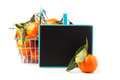 Food basket of tangerines metal full with leaves and empty chalkboard isolated over white Stock Photography