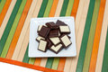 Food collection black and white chocolate a square plate with dark on a napkin of multi colored wooden sticks Stock Photos