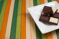 Food collection black and white chocolate a square plate with dark on a napkin of multi colored wooden sticks Stock Images