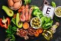Food containing natural vitamin E: Spinach, parsley, shrimp, pumpkin seeds, eggs, avocados, broccoli. Top view.