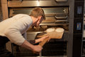 Baker putting dough into bread oven at bakery Royalty Free Stock Photo
