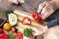 Food, family, cooking and people concept - Man chopping paprika on cutting board with knife in kitchen with daughter Royalty Free Stock Photo