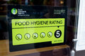 Food hygiene rating a sign on a restaurant window indicating that it has obtained a very good from the united kingdom standards Stock Photos