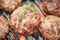 Food meat beef burgers on bbq barbecue grill with flame shallow dof Royalty Free Stock Image