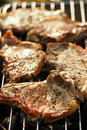 Food meat - marinated juicy pork steaks on grill - summer barbec Royalty Free Stock Photo