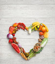 Food photography of heart made from different vegetables on white wooden table. Royalty Free Stock Photo