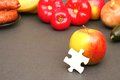 Food puzzle piece leaning on an apple infront of some other focus is on the piece copy space is on the left Royalty Free Stock Photo