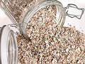 Food: Raw Oats Spilling Out of Glass Jar Royalty Free Stock Photo