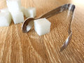 Food sugar cube on foreground with tweezers Royalty Free Stock Image
