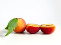Food a whole peach and another cut in two parts in row on white background Stock Photo