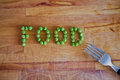 Food word written with peas and a fork Stock Image