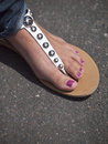 Foot bondage female in leather thong or flip flop as its known in uk background tarmac paving Stock Photos