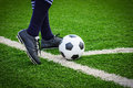 Foot kicking soccer ball on corner field Royalty Free Stock Photos