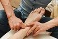Foot massage masseur making a traditional chinese to adult leg and Royalty Free Stock Photos