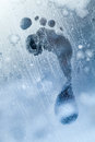 Foot print on frozen windows glass Royalty Free Stock Photo