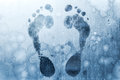 Foot prints on frozen windows glass Royalty Free Stock Photography