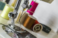 Foot sewing machine with colored threads close up of a needle and needle and thread in the background spools Stock Images