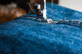 Foot of sewing machine on jeans fabric Stock Photo