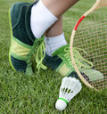 Foot of sportswoman on grass who plays badminton Stock Image