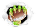 Football claw concept of a monster breaking out of the background holding a Stock Images
