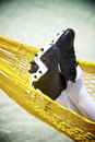 Football cleats soccer player relaxing in beach hammock close up of Stock Image