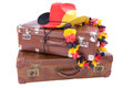 Football cowboy hat over two old suitcases with flower necklace Stock Photography