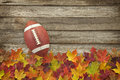 Football with fall leaves on rough wood top view college style and Royalty Free Stock Image