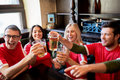 Football fans clinking beer glasses at sport bar