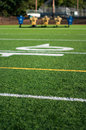 Football field with practice dummy sled in background blocking shallow depth of Stock Image