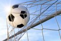 Football goal with sun and blue sky or soccer a neutral design ball flying into the net in the background Stock Photography