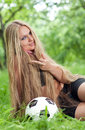 Football hooligan sitting on the grass next to the soccer ball beautiful young woman with long hair sitting around a soccer ball Royalty Free Stock Photography