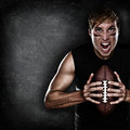 Football player aggressive with american football portrait holding on black blackboard background copy space for text or design Royalty Free Stock Image