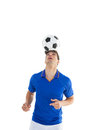 Football player in blue jersey heading ball on white background Stock Photo