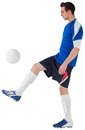 Football player in blue kicking ball on white background Stock Photos