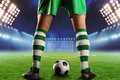 Football player on the football ground with a ball between his legs standing Stock Photo