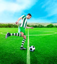 Football player on the football ground kicking ball Stock Photos