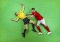 Football player and referee giving red card to a studio shot on a green background Royalty Free Stock Image