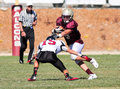 Football player running with the ball during a game from scotts valley high school avoids tackle against aragon high school in Stock Image