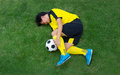Football player in Yellow lying injured on the pitch. Royalty Free Stock Photo
