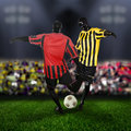 Football soccer competition two players in midfield vie for the ball the stadium is full of supporters Royalty Free Stock Photos