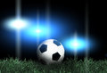 Football and spotlights on green grass Royalty Free Stock Photo