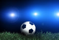 Football and spotlights on green grass Stock Images