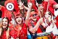 Football supporter fans cheering with confetti watching soccer match cup at stadium tribune - Young people group with red t-shirt Royalty Free Stock Photo