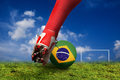 Football world cup soccer player foot hitting a ball with brazilian flag wrapped on it concept Stock Photos