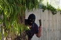 Footpad ambushing behind eucalyptus in black balaclava waiting in ambush with an kitchen hatchet Stock Photo