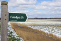 Footpath sign in winter showing direction over snowy marshland at southwold suffolk Royalty Free Stock Photography