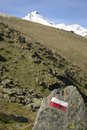 Footpath signposts s red and white on rock leading up to the top of the snowcapped m colombo m in spring season selective focus Stock Photo