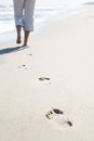 Footprints on the beach lonely woman departing into distance over sea Royalty Free Stock Image